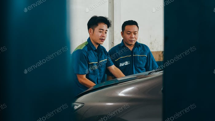 Car mechanic screwing details of car engine on lifted automobile at repair service station.
