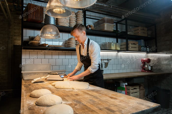baker portioning dough with bench cutter at bakery