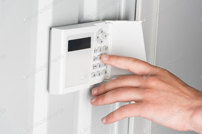 cropped view of person typing password on home security alarm, security system concept