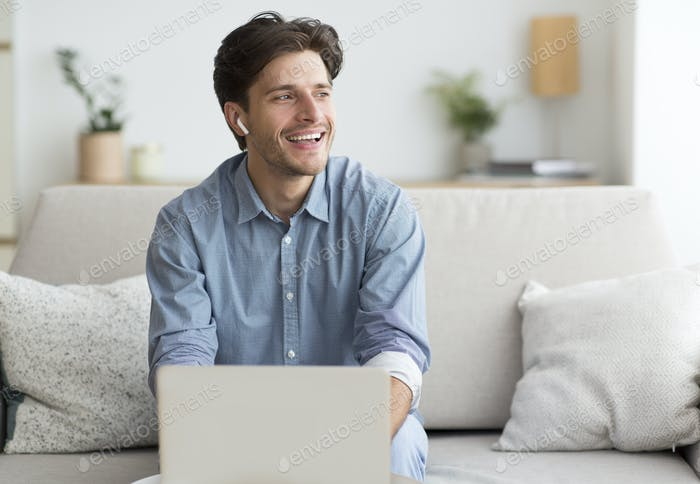 Man In Earphones Using Laptop Sitting On Couch At Home