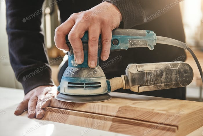 Close up of carpenter polishing wooden board with an orbit sander