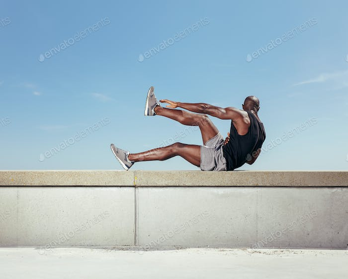 Strong young man exercising outdoors