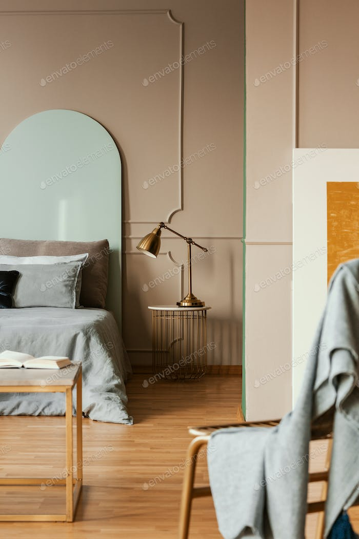 Golden lamp on modern nightstand table next to blue bed in grey bedroom interior