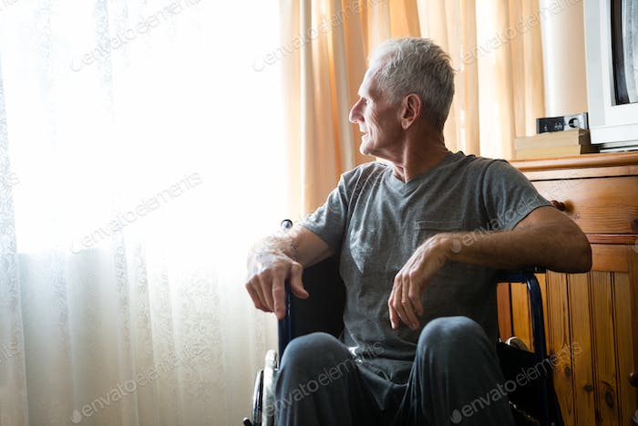 Thoughtful senior man sitting on wheelchair in nursing home