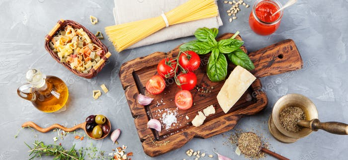Italian food background with vine tomatoes, basil, spaghetti, olives, parmesan, olive oil, garlic