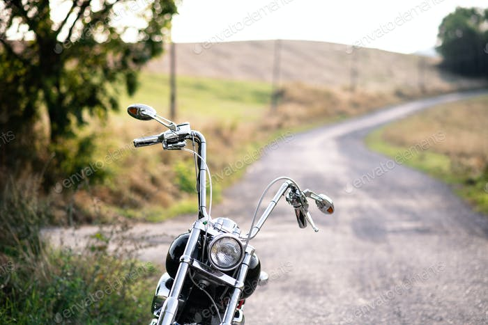 A part of motorbike on road in countryside. Copy space