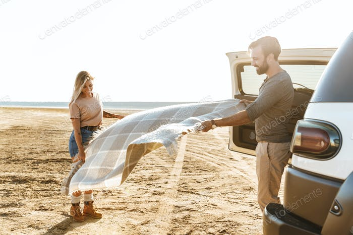 Loving couple outdoors near car with mat litter at the beach.