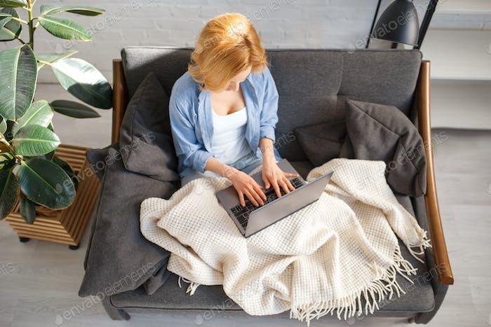 Junge Frau unter einer Decke mit Laptop auf Couch
