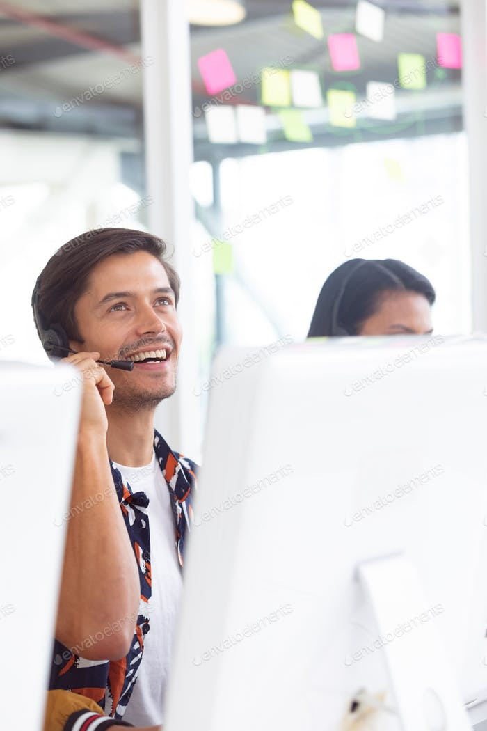 Front view of Caucasian male customer service executive working on computer at desk in office