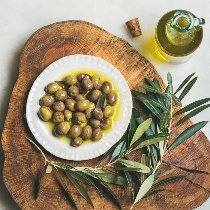 Pickled green Medoterranean olives and olive-tree branch on wooden board