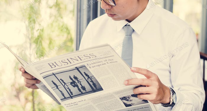 Businessman reading newspaper in the morning