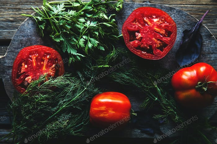 Fresh tomatoes on a dark background. Tomatoes, parsley, dill