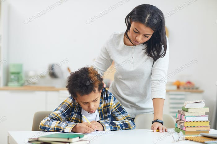 Mutter beobachten Junge Hausaufgaben machen