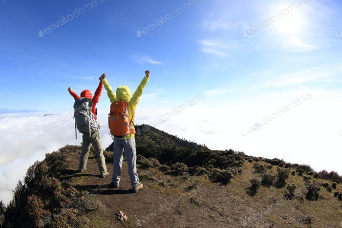 Two successful hiking friends enjoy the view on mountain top
