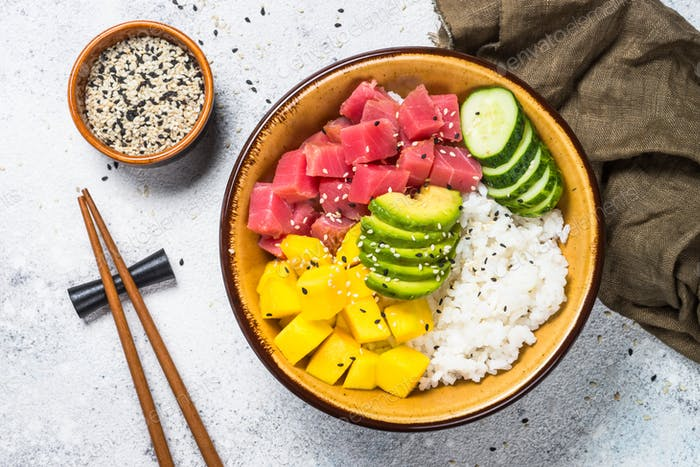 Tuna poke bowl with rice, avocado, mango and cucumber on white table