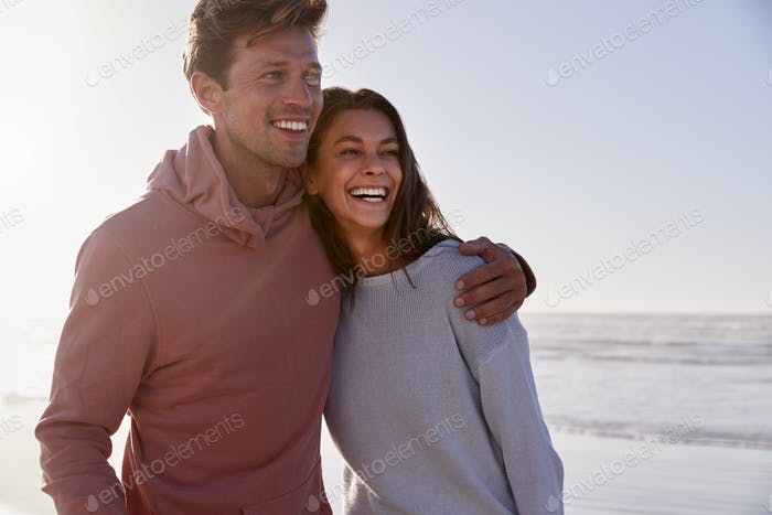Romantic Couple On Walking Along Winter Beach Together