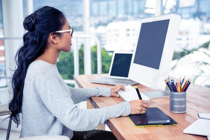 Smiling Asian woman using digital board and computer in office