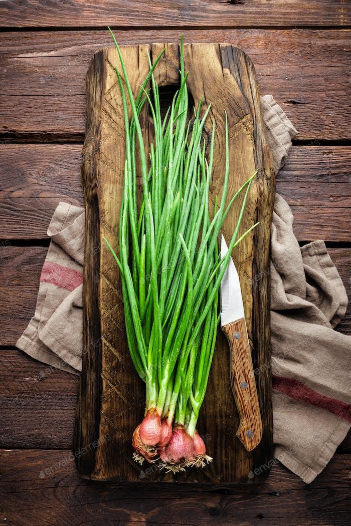 Grüne Zwiebel oder Schalotte auf Holzbrett, frischer Frühlingsschnittlauch