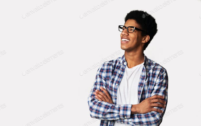 Excited student looking aside with crossed hands, light background