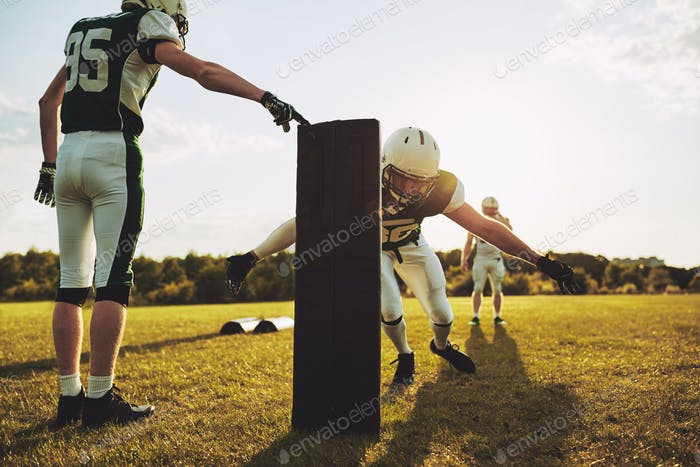American football players doing tackling drills on a football field