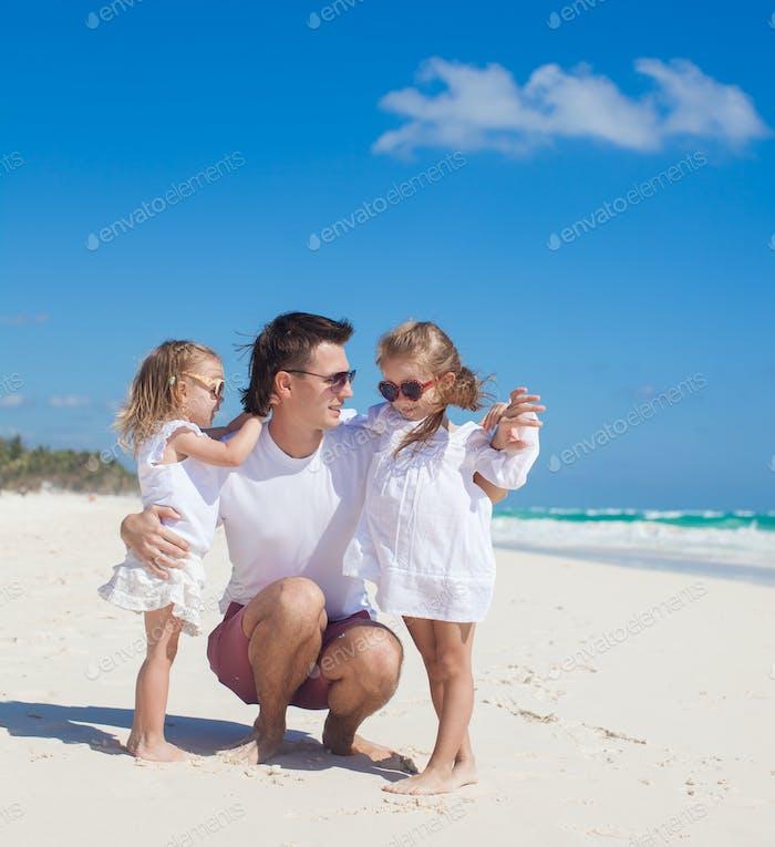 Glücklicher Vater und seine entzückenden kleinen Töchter am sonnigen Tag