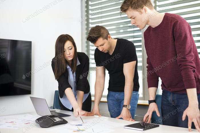 Businesswoman Explaining Plan To Male Colleagues At Desk