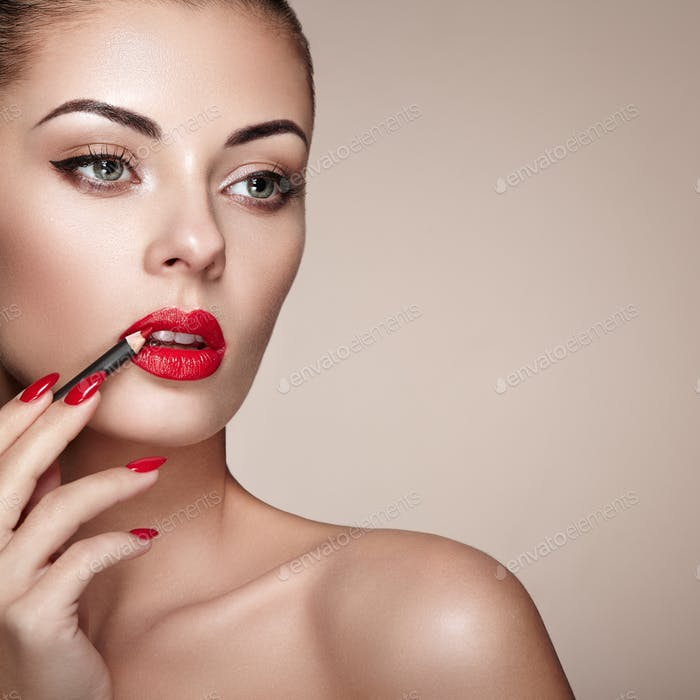 Beautiful woman paints lips with lipstick
