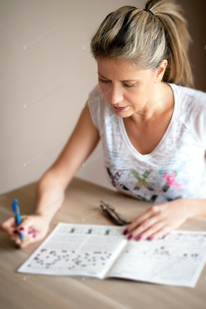 Attractive woman sitting doing crossword puzzles