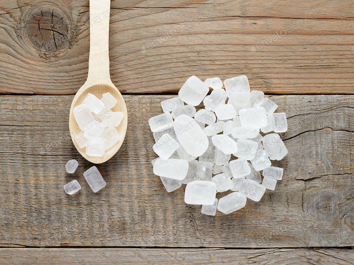 Rock sugar in spoon on wooden background