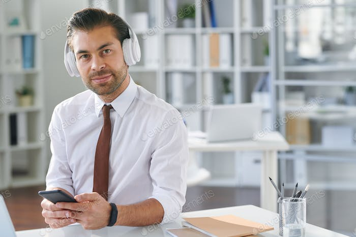 Young well-dressed businessman with smartphone listening to music