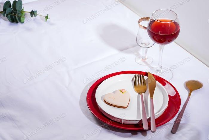 Vajilla y decoraciones para servir una mesa festiva. Platos, copa de vino tinto y cubiertos con corazón