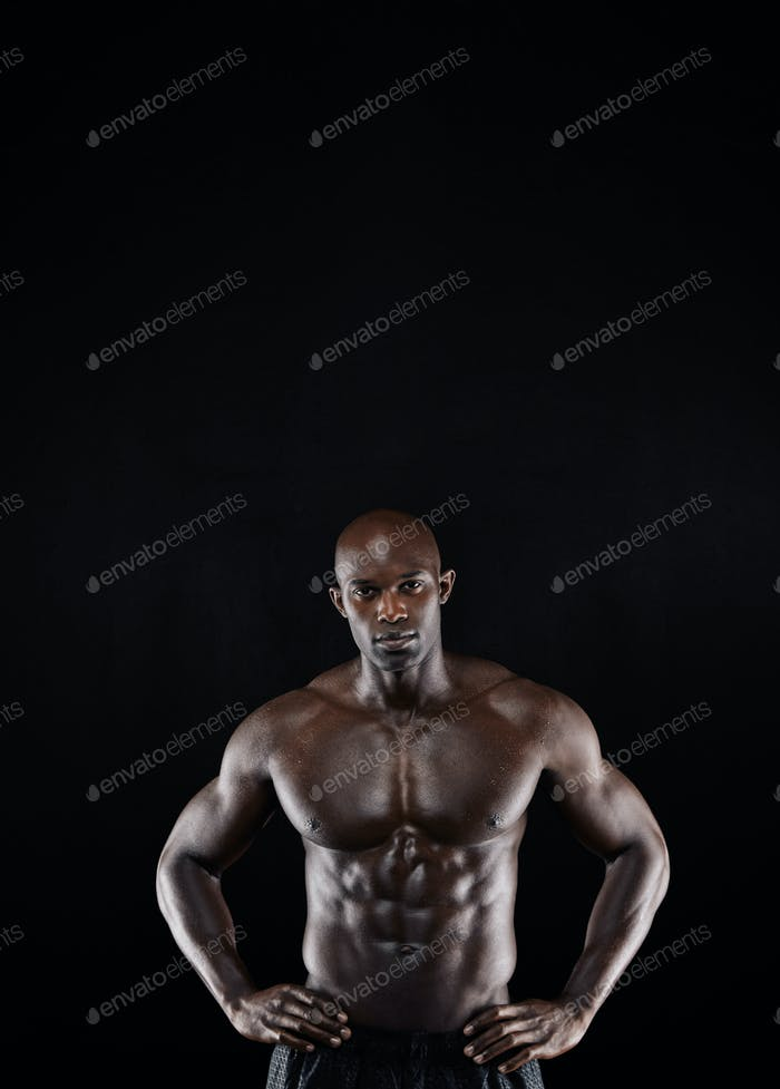 Muscular man posing with his hands on hips