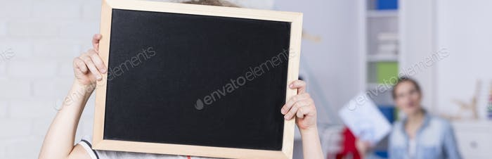 Child holding a blackboard