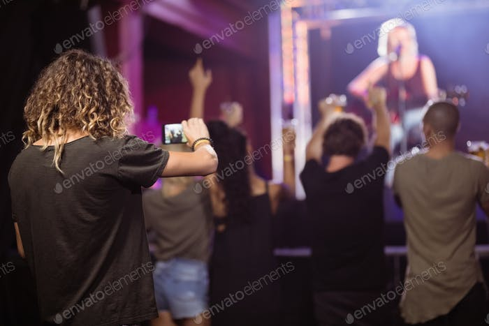 Rear view of man photographing music performance