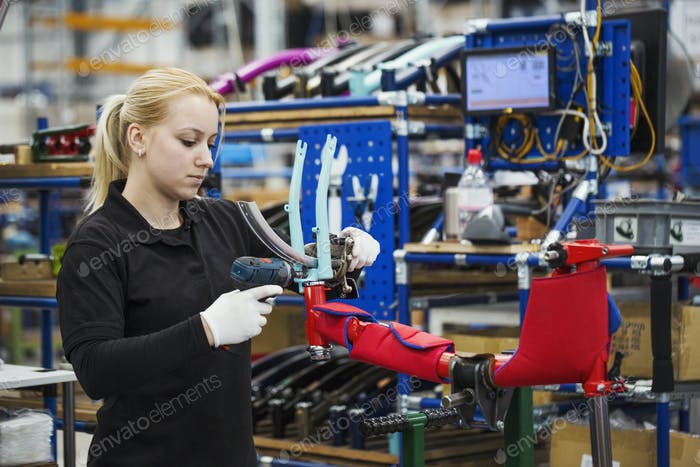 Female skilled factory worker assembling a bicycle handling the brakes assembly and part of the