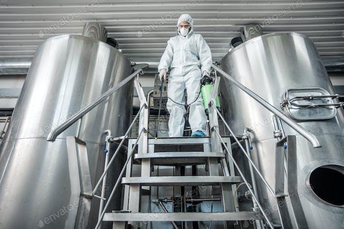 Mann in Schutzanzug, Desinfektion Brauerei Wasserkocher, Freiraum