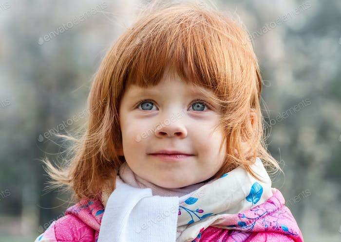 Portrait of a beautiful little girl in the park