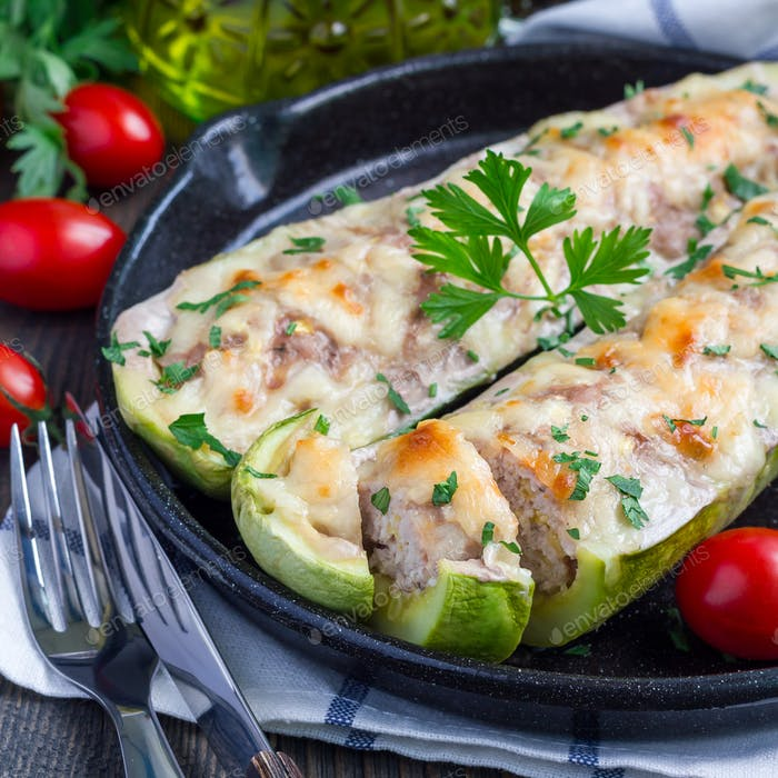 Zucchini boats stuffed with ground meet and topped with cheese on cast iron pan, square format