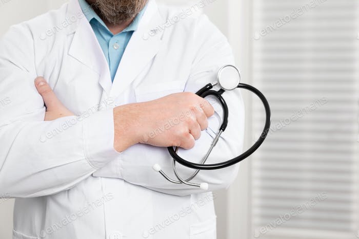 Close-up of a male doctor holding stethoscope in the office