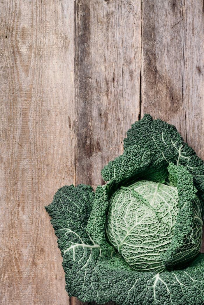 Rohes Grünkohl Textur. Bio Wirsing auf Holzhintergrund. Ansicht von oben Leerzeichen kopieren. Vegan