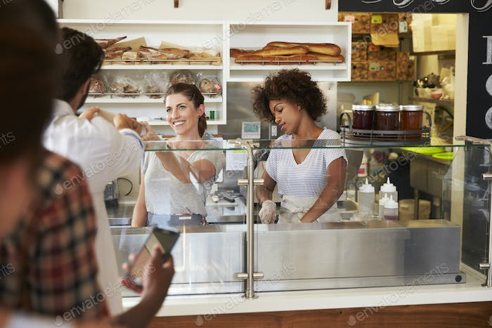A queue of customers served by two women at a sandwich bar