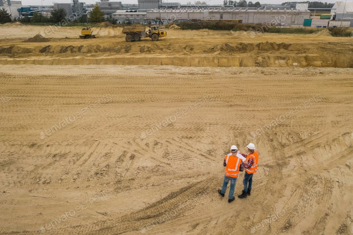 Two road construction workers in orange vests and protective helmets in the middle on the field