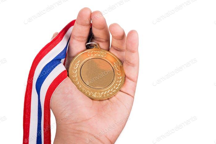 Athlet hält Goldmedaille mit Band auf der Hand