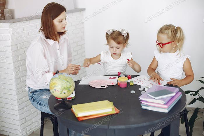 Tutor with two little girls studying at home