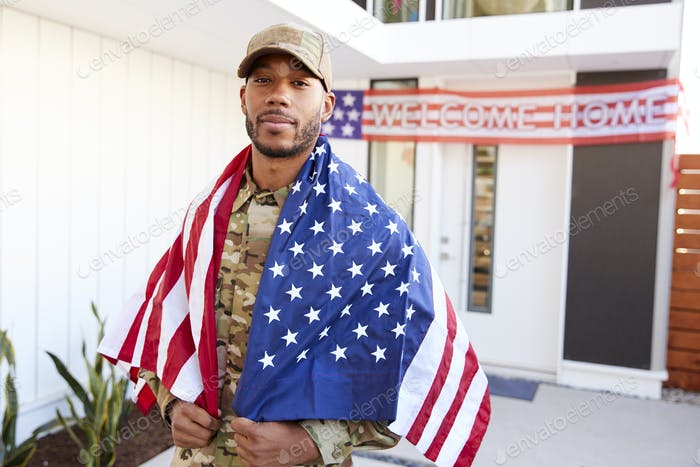 Millennial black soldier with US flag draped over his shoulders, looking to camera, close up