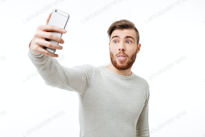 Surprised casual young man taking selfie and showing tongue over white background