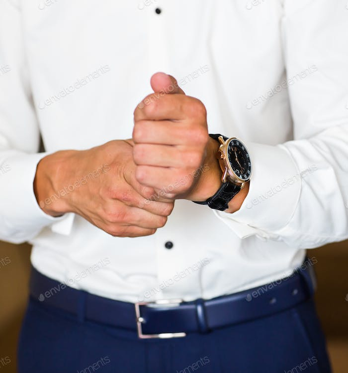 businessman puts on a watch