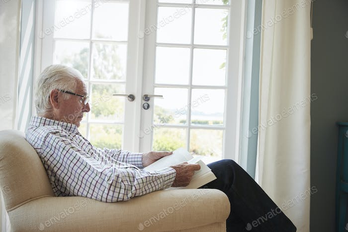 Senior man sitting in an armchair reading a book, close up