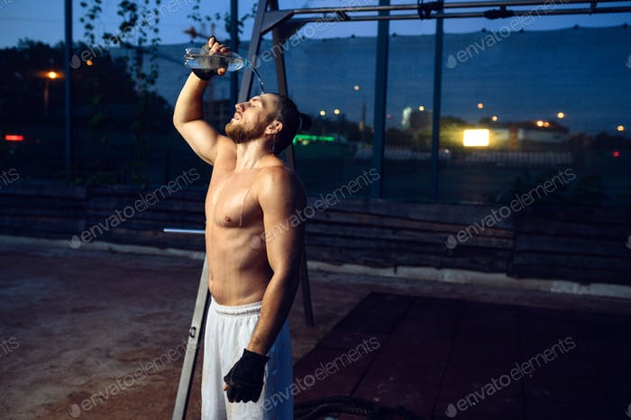 Tired man doused with water, street workout
