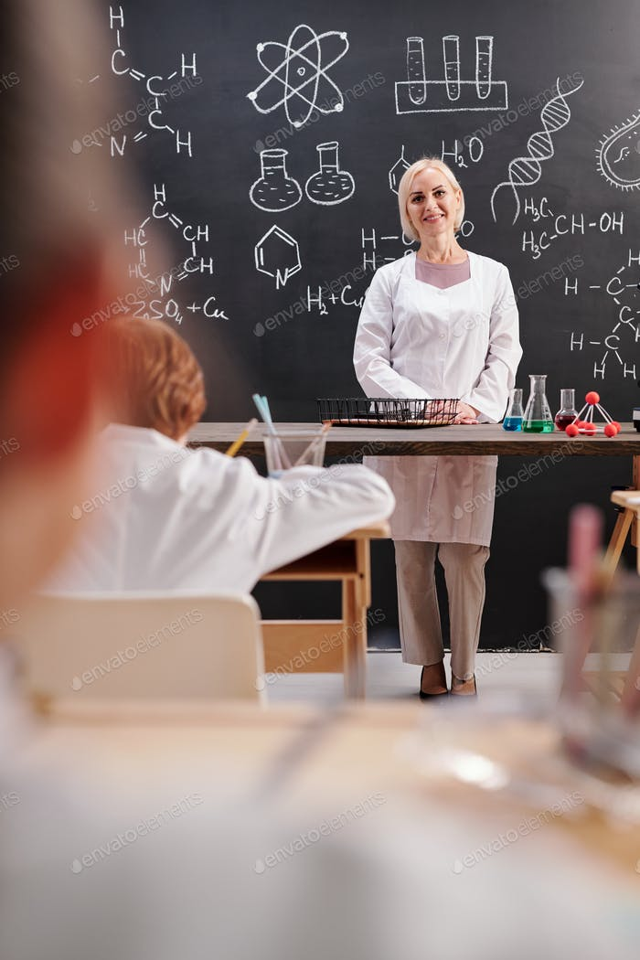Young blond cheerful teacher of chemistry in whitecoat standing by blackboard